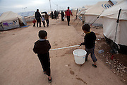 Syrian refugee children carry a leaking bucket of water at  the Za'atri Syrian refugee camp in northern Jordan February 5,2013. ..Jordan announced on Tuesday that the number of Syrian refugees in the country is expected to exceed 700, 000 in 2013, the state-run Petra news agency reported. (Photo by Heidi Levine/Sipa Press).