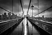 Two umbrellas on the Brooklyn Bridge on a rainy day, new York