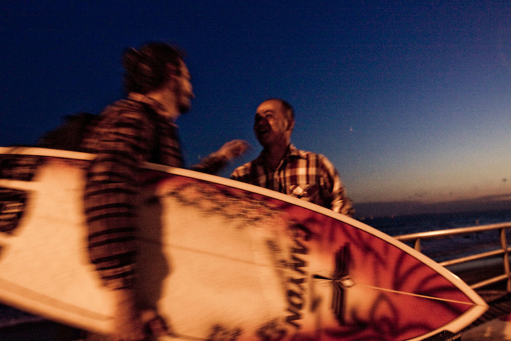 Two surfers say goodbye after an early evening surf session, Rockaway Beach, Queens, NY.