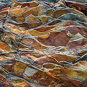 """Billion-year-old rock breaks into a jagged pattern in Glacier National Park, Montana. Published in """"Light Travel: Photography on the Go"""" book by Tom Dempsey 2009, 2010. Since 1932, Canada and USA have shared Waterton-Glacier International Peace Park, which UNESCO declared a World Heritage Site (1995) containing two Biosphere Reserves (1976). Rocks in the park are primarily sedimentary layers deposited in shallow seas over 1.6 billion to 800 million years ago. During the tectonic formation of the Rocky Mountains 170 million years ago, the Lewis Overthrust displaced these old rocks over newer Cretaceous age rocks."""