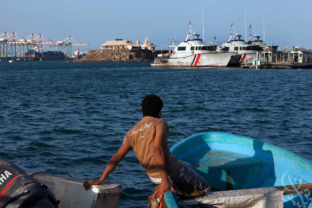 A Yemeni fisherman looks out over Yemeni Coast Guard patrol boats April 13, 2010 in the port of Aden, Yemen. A small fishing boat like this one was used in the infamous suicide bombing attack on the United States Navy Destroyer the USS Cole in the port of Aden in 2000.
