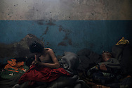 An unaccompanied minor from Afghanistan is seen where he is spending his nights waiting to cross the European borders. He is living in the warehouse of Belgrade where thousands are surviving in the dark smoke, without sanitation and choked by the cold weather.