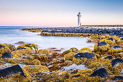 Port Fairy Lighthouse on Griffith Island. The image was taken at low tide when yellow seaweed on the rocks are exposed. Waves lapping the rocks have been rendered to a mist by using a long exposure and stacking of multiple images.