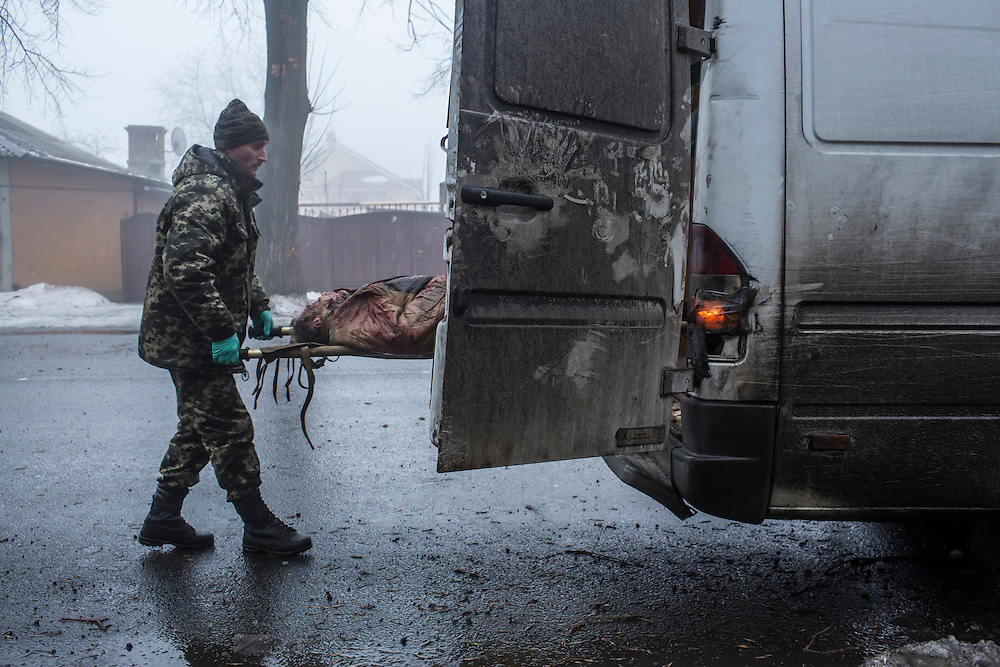 DONETSK, UKRAINE - JANUARY 30, 2015: The body of a man killed when a rocket or mortar landed on the road and exploded nearby is removed for transport to the morgue in Donetsk, Ukraine. At least two men were killed at the scene while on the sidewalk. At least five other people were killed in a separate attack nearby when a rocket struck the parking lot outside a center for the distribution of humanitarian aid. CREDIT: Brendan Hoffman for The New York Times