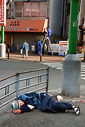 Homeless man sleeping on the street in Airin..The old name of the area now called Airin, was untill 1966 Kamagasaki and many people still call it like that. .Kamagasaki (????) is an old place name for a part of Nishinari-ku in Osaka, Japan. Airin-chiku (???????) became the region's official name in May, 1966.Sections of four different towns: Nishinari-ku Taishi (??????), Haginochaya (?????), Sanou (???), North Hanazono (????) and Tengachaya (?????) are collectively known as the Kamagasaki region..Kamagasaki as a place name existed until 1922. Kamagasaki is known as Japan's largest slum, and has the largest day laborer concentration in the entire country. 30,000 people are estimated to live in every 2,000 meter radius within this region. An accurate count of occupants has never been produced, even in the national census, due to the large population of day laborers who lack permanent addresses..