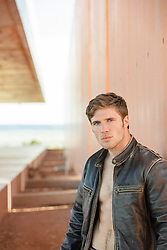 hot man in a leather coat without a shirt at a modern home
