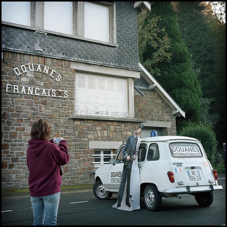 Le 23 octobre 2011, frontière Belgique / France, village de Macquenoise (B), RN 99. Devant l'ancien poste frontière français, une touriste française photographie la voiture du  film «Rien à déclarer» tourné sur la frontière franco-belge de Macquenoise, après avoir visiter les lieux du tournage.