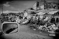 Children, who live rough on a major roadside in the port section of Manila's Tondo in makeshift shacks just a meter or two above sea level, watch rush hour traffic over garbage piled high along the curb..  Squatters have now lived in Manila this way, in the photographer's observation, for more than two generations and, since global warming is bringing ever stronger typhoons, and rising sea levels, scientist suggest that this entire district may need to be evacuated in the not too distant future.<br /> <br /> On Maplecroft's Climate Change Vulnerability Index, Manila ranks as the world's second most vulnerable city to climate change.  Manila's Tondo is Manila's district most vulnerable to climate change-induced sea rises, storm surges from increasingly strong typhoons and earthquake trigger tsunami.  It has a population density of nearly 78,000 people per square km (202,800 ppl/sq mi), according to a 2009 Cornell University report.  (Note: Manhattan has a population density of 26,939/km2 [69,771/sq mi].)
