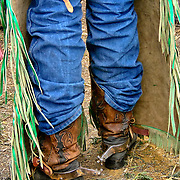 This is a rodeo cowboy and his spurs are designed to help him stay on a bucking bull. His chaps have long fringes for more flash during his ride.