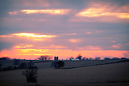 The sun sinks through a layer of clouds on a cool fall afternoon on the plains near Miledgeville, IL.