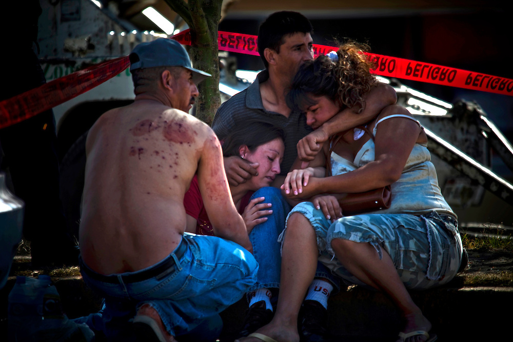 A family grieves at the scene of a murder of a family member in Ciudad Juarez, Chihuahua on May 20, 2010.