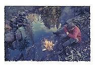 Norwegian boy sitting by camp fire