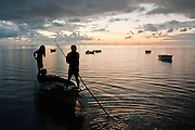 Fishermen set out for night fishing from a south coast pier on a rainy evening.