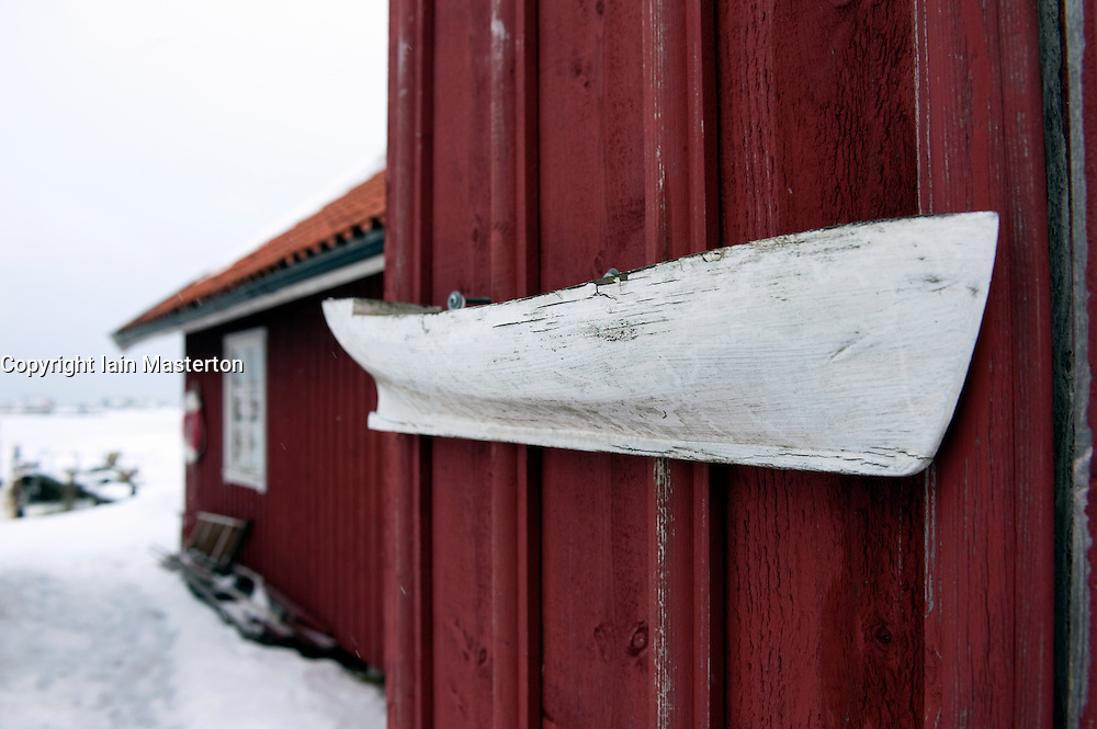 Small old wooden boat hanging on wall of redboathouse in Fiskebackskil on Bohuslan coast in Vastra Gotaland Sweden