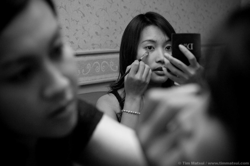 Manager Yo checks her makeup while Doi, a transgendered woman, does the makeup for 12 girls of in section eight of the Violin Karaoke Bar in Chiang Mai, Thailand. Doi's day job is as staff at M Plus, an NGO providing a health clinic for sexually transmitted infections and a community center for gay, transgendered, and male sex workeres. In the evenings Doi's responsibility is the makeup for the girls of section eight for which she earns 1000 Baht per person per month; at about 12,000 Baht ($370 USD) this job nets her double the average Thai salary. From 7-9pm young women, ages 15 to 22, prepare for a night of work. Their job is to sell drinks to customers who book the karaoke rooms; in the neighboring dance club, also part of the Violin, there are cocktail waitresses. However, many are also freelance sex workers or 'bar girls' who make their own arrangements with the customers for a 'date.' Most of the customers are asian; they are either Thai, Korean, Chinese, or Japanese.