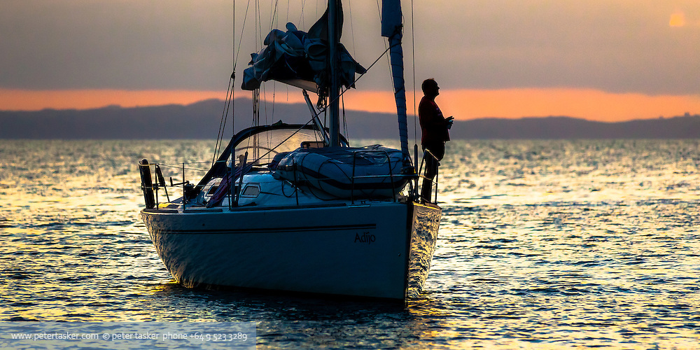 Yachtie on Adijo enjoying a sunset. Elephant Cove, Coromandel Peninsula, Hauraki Gulf, New Zealand. Waiheke Island in background.