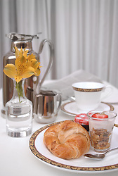 Continental breakfast with croissant, yogurt and coffee in a vertical format