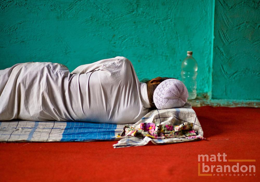 A man takes a midday nap inside a small Muslim shrine.