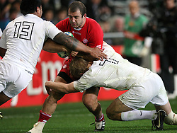 Georgia's Jaba Bregvadze, centre, in the tackle of England's Manu Tuilagi, left, and Lewis Moody in the Rugby World Cup pool match at Otago Stadium, Dunedin, New Zealand, Sunday, September 18, 2011. Credit:SNPA / Dianne Manson.