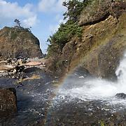 A manmade flume spews a waterfall and creates a rainbow near a sea stack island, on a beach immediately south of Cape Meares, on the Oregon coast, USA.