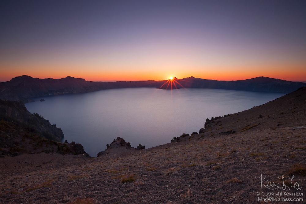 The sun sets behind the rim of Crater Lake in this view from the Cloud Cap Overlook in Crater Lake National Park, Oregon. Crater Lake, which is actually a caldera, formed when Mount Mazama erupted violently about 7,700 years ago, causing its summit to collapse. Subsequent eruptions sealed the caldera, trapping rain water and snowmelt, forming the lake, which has a maximum depth of 1,949 feet (594 meters). Wizard Island, a volcanic cinder cone, is visible in the lake just beneath the sun; Phantom Ship, another remnant of volcanic activity, is visible as an island on the left side of the image.