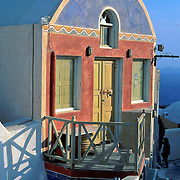 Oia, Santorini Island, Greece: colorful red, yellow, and blue shop with porch.