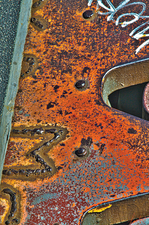 Rust with graffiti and welds, abstract.