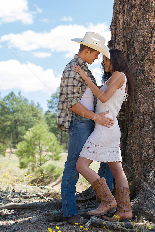 cowboy and a sexy girl holding one another outdoors