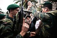 TUNISI. UN CITTADINO TUNISINO SI AGGRAPPA AL BRACCIO DI UN SOLDATO DURANTE UNA MANIFESTAZIONE PUBBLICA CONTRO IL PARTITO RCD DELL'EX PRESIDENTE DELLA TUNISIA BEN ALI;