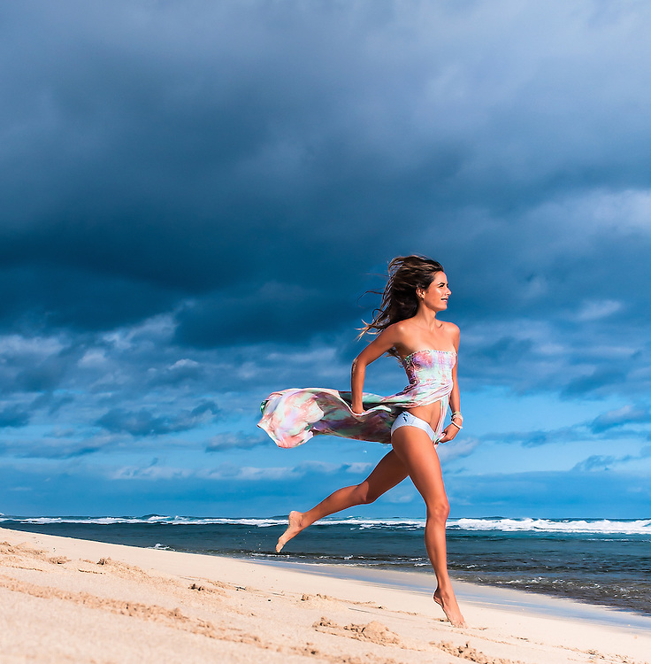Woman on the beach in Hawaii wearing the Tiare Hawaii Over the Rainbow Dress. <br />