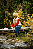 Woman uses laptop computer on bridge over creek, San Isabel National Forest, Colorado, <br /> MODEL RELEASED