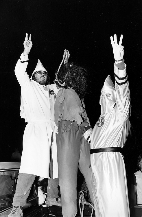 """Flashing the """"W"""" or """"white power"""" symbol, Ku Klux Klan members simulate the lynching of an African American with a gorilla masked dummy at a Klan Rally outside Jackson, Georgia. The rally - held in a rural farm field - attracted about 125 people and attempted to both incite violence against blacks and enlarge the local KKK membership."""