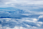 Mount Rainier, the highest point in Washington state and the tallest volcano in the Cascade Range, pokes out from between layers of clouds in this aerial view.