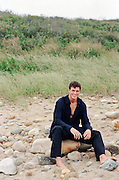 man sitting on the a rocky beach in East Hampton,NY