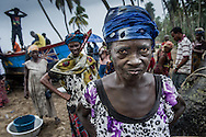 Woman buying freshly caught fish at Jarway Wharf in the town of Ewe, Ghana.  Here fishermen come ashore to sell their fish.