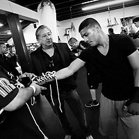 Bantamweight world champion boxer Abner Mares gets his gloves taken off as manager Frank Espinoza, center, talks to him about an upcoming fight.