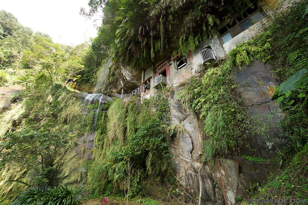 A remote temple sits high on a cliff next to a waterfall in the lush forest of northern Taiwan.