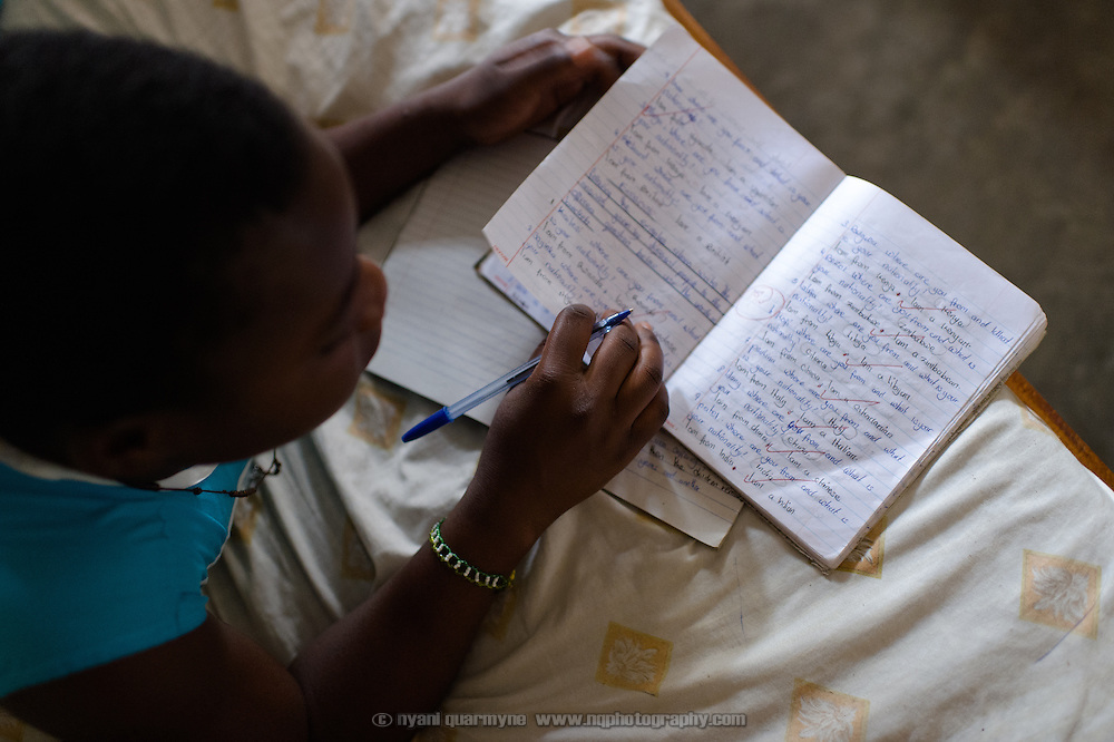 "Peninah Mamayi, the Health Prefect at Achilet Primary School near Tororo in Eastern Uganda, revising for exams at her home on 1 August 2014. As Health Prefect she educates her peers on a range of health and hygiene issues, including menstrual hygiene. She says, ""I wanted to be a health prefect so I could help my friends be clean. I teach them about cleaning their latrines at home, keeping their compounds clean at home, cutting their hair and fingernails, washing their clothes. I tell them that after they pick rubbish they should wash their hands. I tell them to be bathing daily so that they don't smell. And to wash their Afripads very well, and to dry them very well."" An Afripads customer herself, she says Afripads (locally manufactured reusable sanitary pads) ""have improved my life because they don't disturb me, and I can just sit and be comfortable. Even if I play or I jump, nothing happens."""