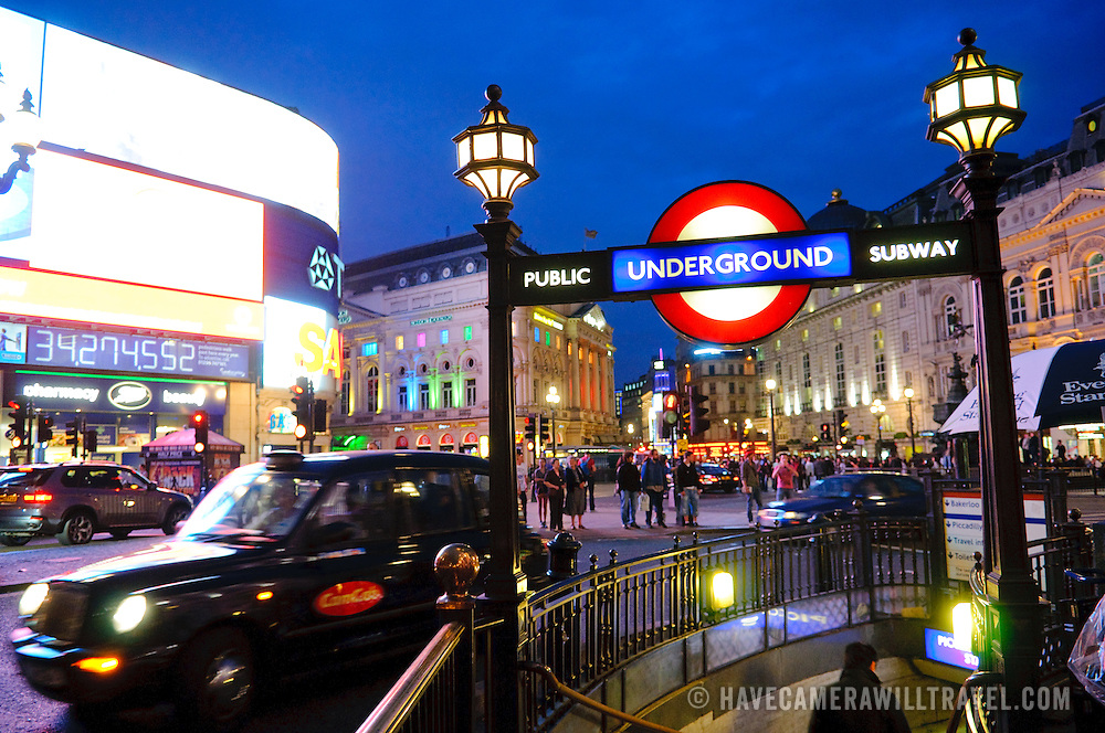 The busy traffic at Piccadilly Circus in the heart of London, at night. To the right is a London Underground entrance and sign and at right is a London Taxicab and some of the advertising lights. Editorial use only.