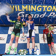 Brad White, center, of team United Health care Pro cycling  celebrates celebrate on the podium in front of the Grand Opera House on Market Street after winning the Men's Pro & Category I (35 miles) race for the third consecutive time in three years Saturday, May 14, 2016, in Wilmington Delaware.