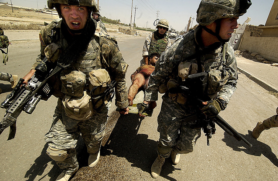 SPC Thadeus McPheron, an interpreter and SSG Eric Forbes from Bravo Company 2-6 Infantry, Task Force 1-35 from Baumholder Germany, evacuate an injured Iraqi man shot in the leg after a suicide car bomb explosion at an intersection in Tameem, Ramadi, Iraq on August 10, 2006. The soldiers from Bravo Company 2-6 Infantry, Task Force 1-35 from Baumholder Germany, were performing a routine patrol at an intersection in Tameem, a suburb of Ar Ramadi when a suicide car bomb exploded about twenty five meters in front of the patrol. Initial reports indicated that two were killed (one civilian and the bomber) and four were wounded (one Iraqi Police Officer and three civilians). Immediately after the explosion, Soldiers of Bravo Company cordoned off the area, treated and evacuated the wounded and maintained security until an Explosive Ordinance Disposal team (EOD) arrived to clear the area.  One civilian died of wounds at the treatment facility.  While EOD was on scene, the patrol took small arms fire from outside of the cordon.  EOD recovered one 110mm artillery round and three 115mm rounds that were believed to be connected with detonation wires from the dashboard of the vehicle. — © TSgt Jeremy Lock/
