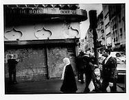 23..Maghrebi Muslim family walk past shuttered Jewish shop no longer in business, Belleville.