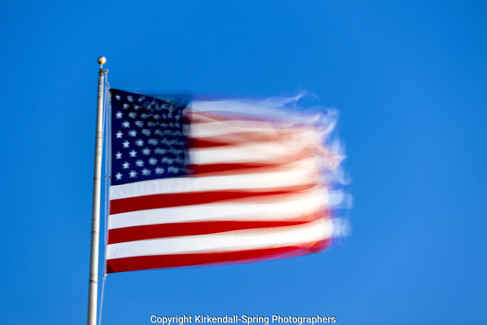 NC00902-00...NORTH CAROLINA - United States Of America Flag blowing in a strong wind.
