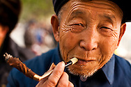 Man smoking a traditional handrolled cigarette with cigarette holder in Chengdu
