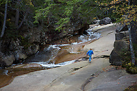 A boy walking on the rocks along side of a river in the White Mountains, NH.