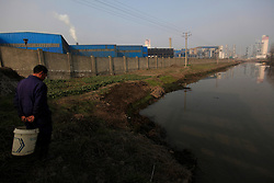 A villager from Dongtan Village looks at the putrid river that separates his village from the Jinhuarun Chemical Industry plant in a chemical industry park in Zekou Town, Qianjiang City of Hubei Province, China 14 January 2013. The villagers used to use the water and fish from the river before the arrival of the chemical plants but now the river is so polluted from discharge by the factories that they can no longer find any fish in it. While the heavy smog in Beijing and much of northern China in recent days have caused alarm among residents and renewed scrutiny on the pollution woes of the country, villagers in a small town of Hubei Province have been grappling with severe air, water and noise pollution on a daily basis over the past two years. China's Xinhua news reported 04 January 2013 that more than 60 cancer deaths in various villages of Zekou Town has been caused by the heavy pollution from the chemical industry park nearby. About 20 or more chemical plants built around the villages of Dongtan, Xiangnan, Zhoutan, Sunguai, Qingnian and others over the past two years has created huge increases in noise, air and water pollution. Many villagers complained of intensifying respiratory, heart, skin and circulatory illnesses caused by the pollution and a large spike in cancer diagnoses and deaths since the factories were built. .