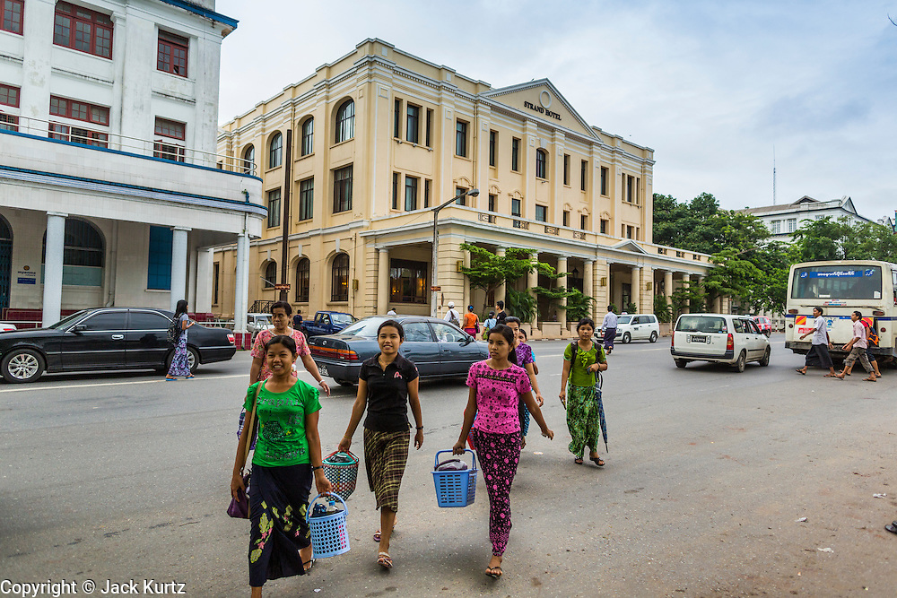07 JUNE 2014 - YANGON, MYANMAR: Women cross the street in front of the Strand Hotel. The Strand Hotel in Yangon is now one of the most expensive hotels in Yangon. It opened in its current location in 1901 and is one of the jewels of Yangon's colonial architecture. Yangon has the highest concentration of colonial style buildings still standing in Asia. Efforts are being made to preserve the buildings but many are in poor condition and not salvageable.    PHOTO BY JACK KURTZ