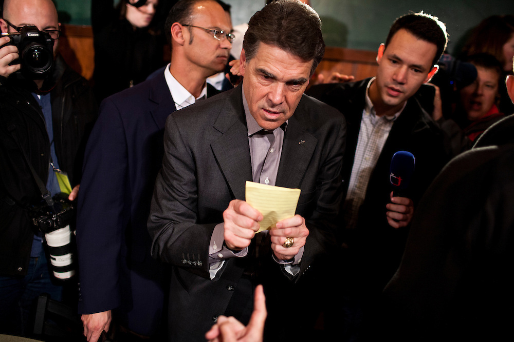 Republican presidential candidate Rick Perry talks with patrons at a campaign event at the Fainting Goat on Friday, December 30, 2011 in Waverly, IA.