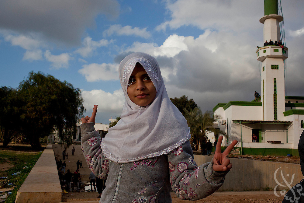 A Libyan girl flashes victory signs while touring the looted and abandoned Katiba el Fedeel Boummar military base with her family in Benghazi Libya February 26, 2011. There are unconfirmed reports a rebel force, made up of defected soldiers and volunteers,  is moving closer to the capital Tripoli.. Slug: Libya.Credit: Scott Nelson for the New York Times