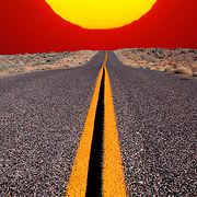 Setting sun over desert road with double yellow center line
